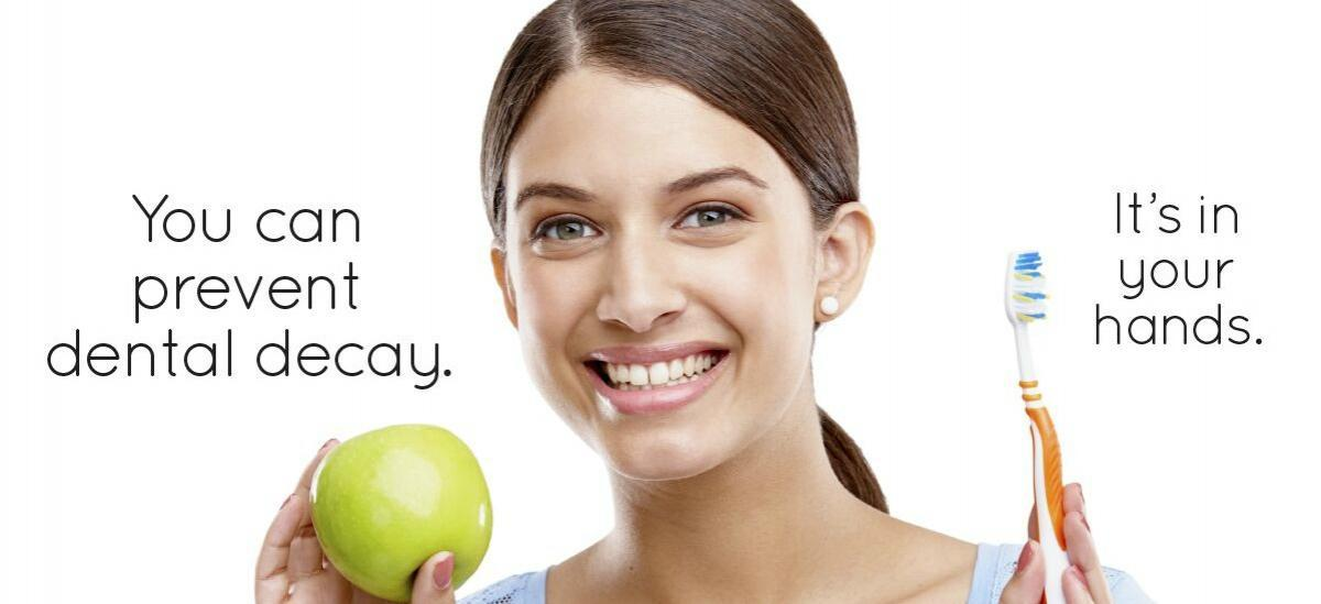 woman smiling holding an apple and a toothbrush