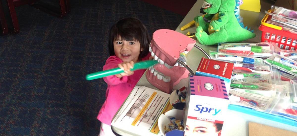 little girl playing with over sized toothbrush